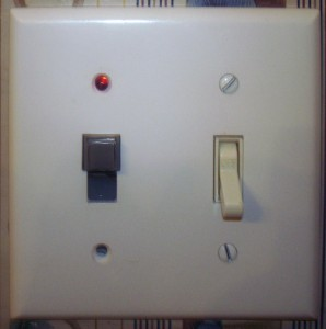 Modified push button switch in light switch faceplate